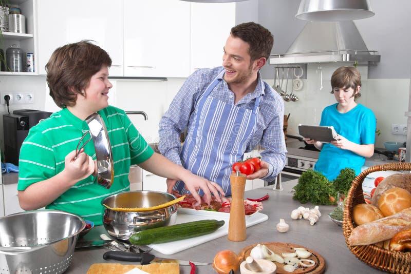 Avla matlagning med hans barn i köket - familjeliv arkivbild