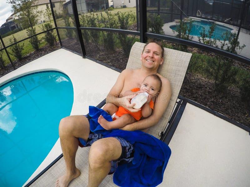 Avla matning hans förtjusande son av en flaska, medan sitta vid simbassängen arkivbilder