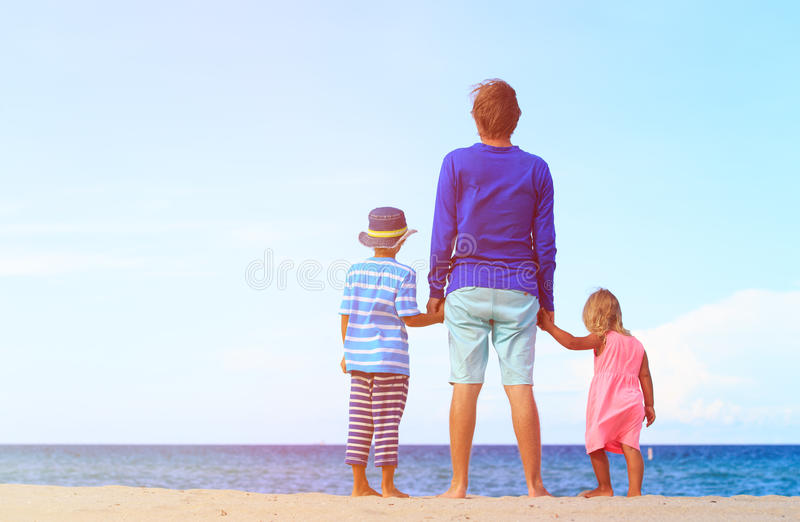 Avla med den lilla sonen och dottern som går på stranden royaltyfri foto