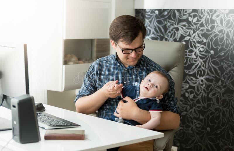 Avla med hans behandla som ett barn sonen som arbetar på kontoret royaltyfri fotografi