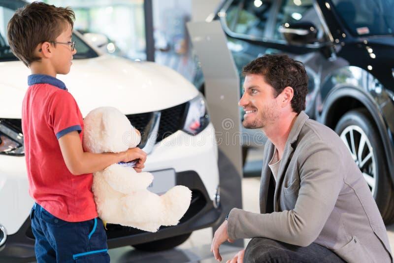 Avla med sonen i automatisk för visningslokal för bilåterförsäljare köpande royaltyfria foton