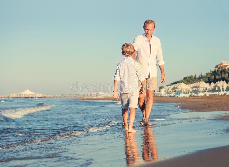 Avla med sonen som tillsammans går på havssurflinen royaltyfri foto