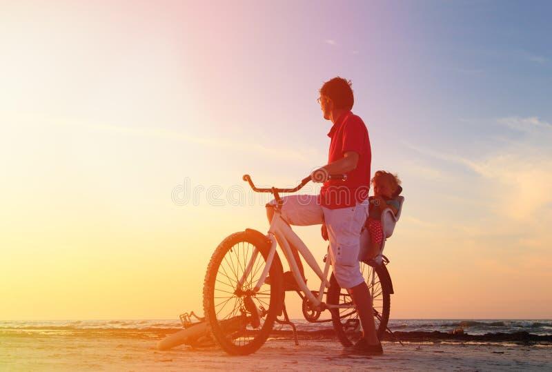 Avla och behandla som ett barn att cykla på solnedgången royaltyfria foton