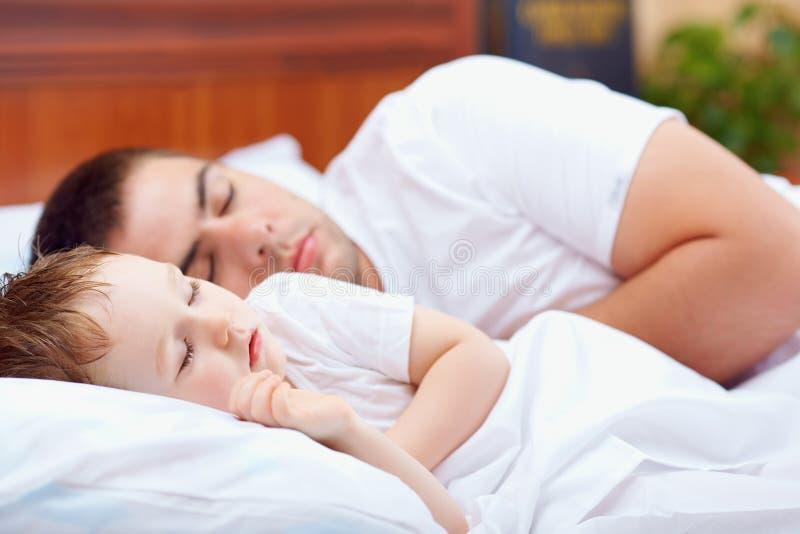 Avla och behandla som ett barn att sova i säng royaltyfri fotografi