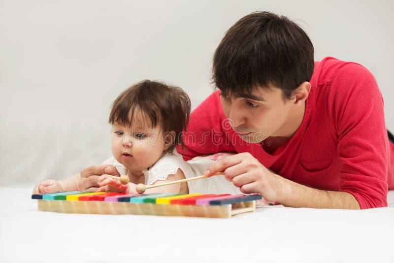 Avla och behandla som ett barn flickan som hemma spelar xylofonleksaken royaltyfri bild