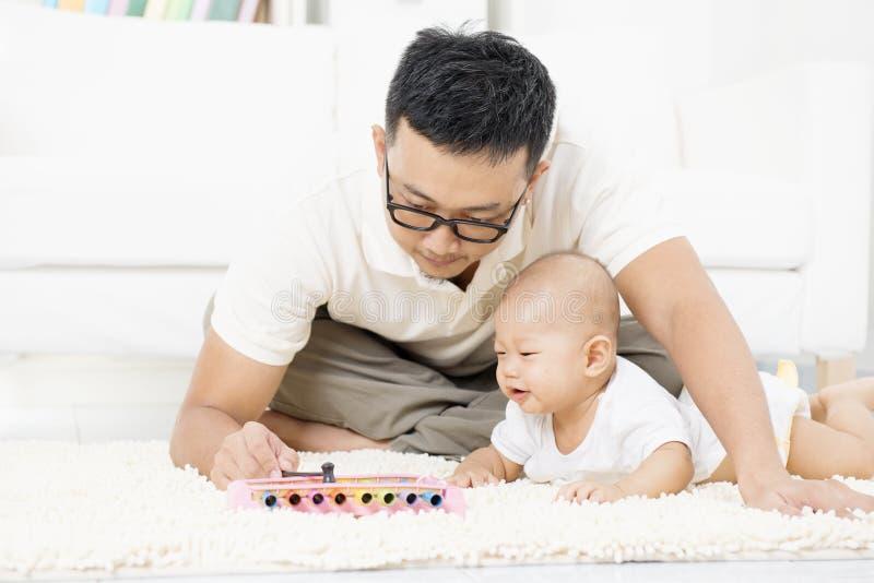 Avla och behandla som ett barn spela musikinstrumentet arkivbild