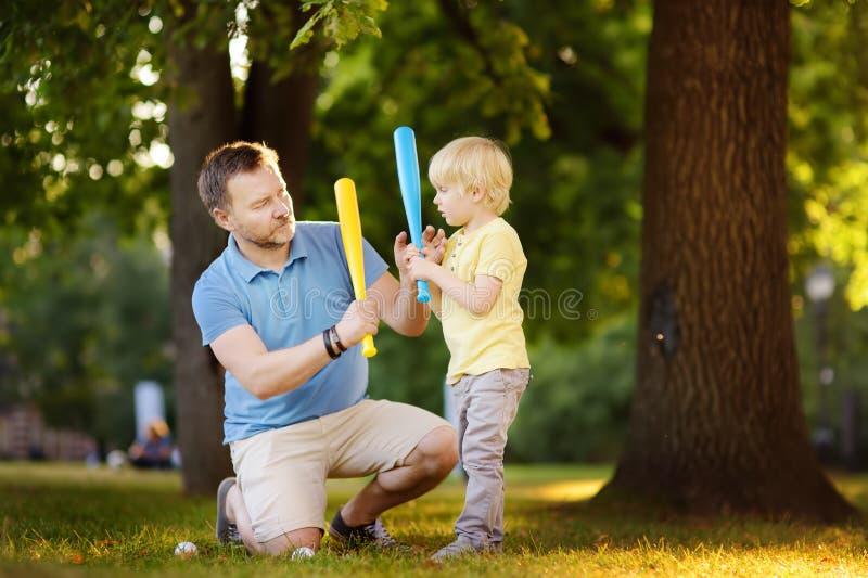 Avla, och hans son som spelar baseball parkerar in royaltyfri foto