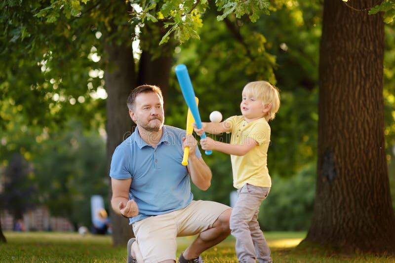 Avla, och hans son som spelar baseball parkerar in arkivfoton
