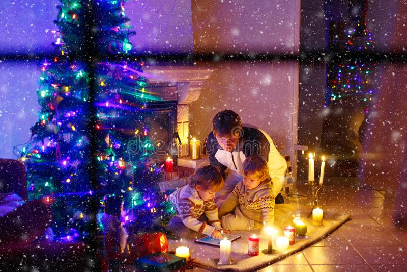 Avla och hans tv? lilla barn som sitter vid spislampglaset p? julaftontid Spela f?r farsa- och ungepojkes?ner arkivbilder