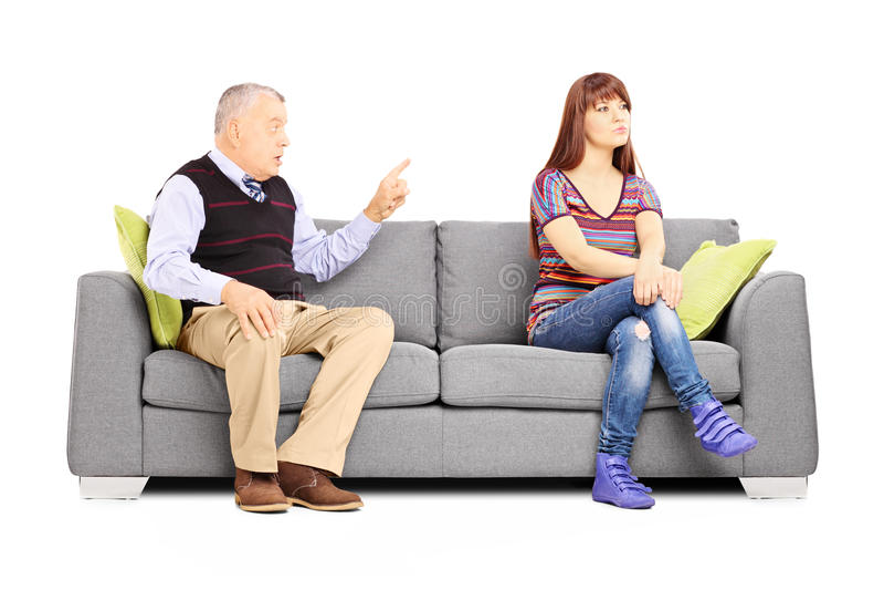 Avla reprimending av hans ointresserade dotter som placeras på en soffa royaltyfria bilder