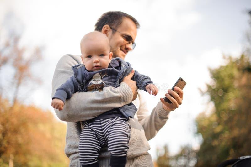 Avla sonen för innehavet lite och att kontrollera telefonen royaltyfri foto