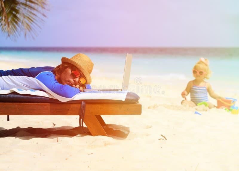 Avla sovande på bärbara datorn medan barnlek på stranden royaltyfri foto