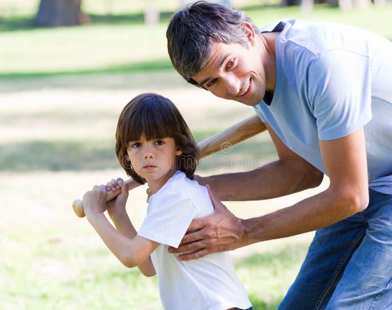 Avla undervisa hans son hur man play baseball arkivfoto