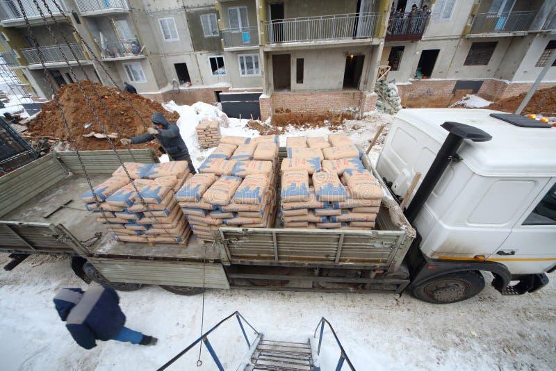 Avlastning av cement från en lastbil till konstruktionen royaltyfri foto