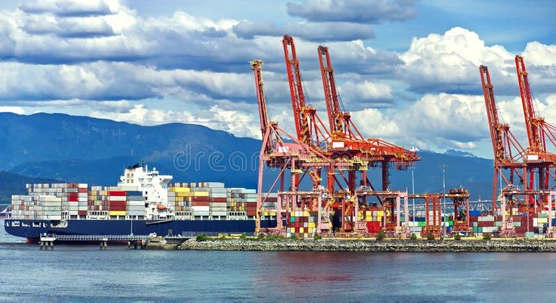 Avlastning av containerfartyg i Vancouvers hamn, röda sjökranar och färgade behållare med grumlig himmel arkivfoton