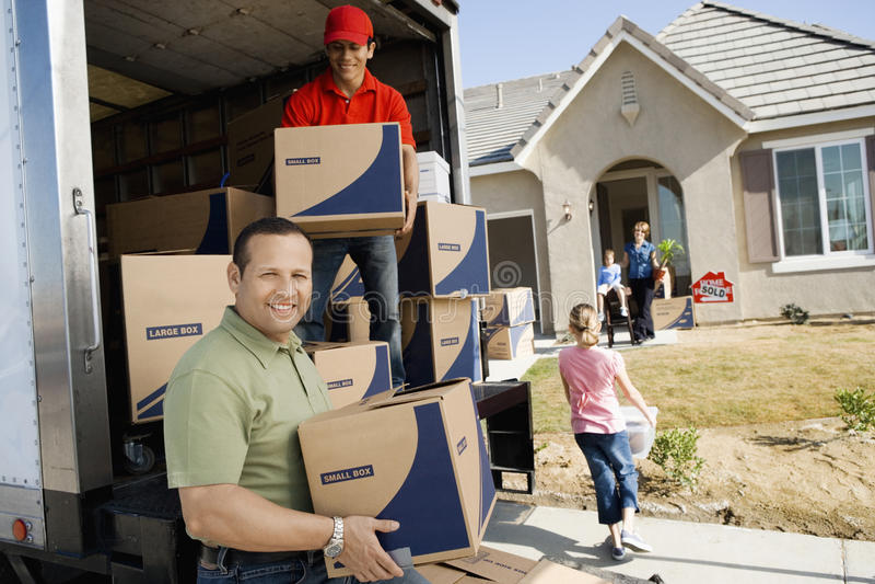 Avlastning av leveransen Van In Front Of House arkivfoton