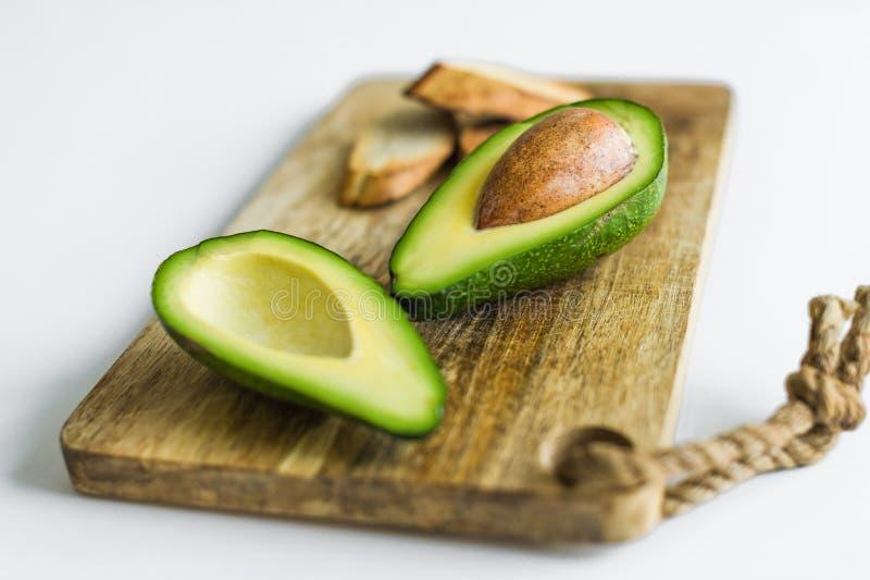 Avocado affettato sul tagliere di legno immagini stock