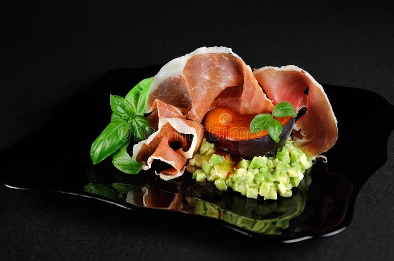 Avocado with apricot and Parma ham royalty free stock photography