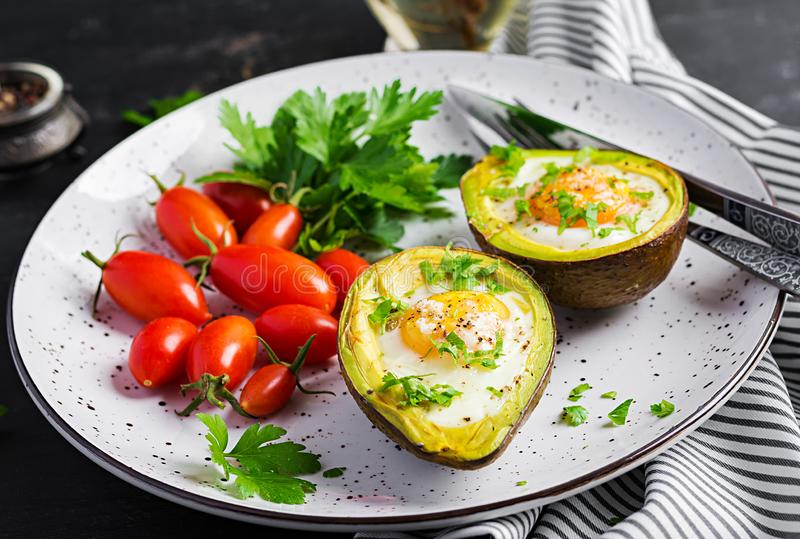 Avocado baked with egg and fresh salad. Vegetarian dish. Ketogenic diet. Keto food royalty free stock image