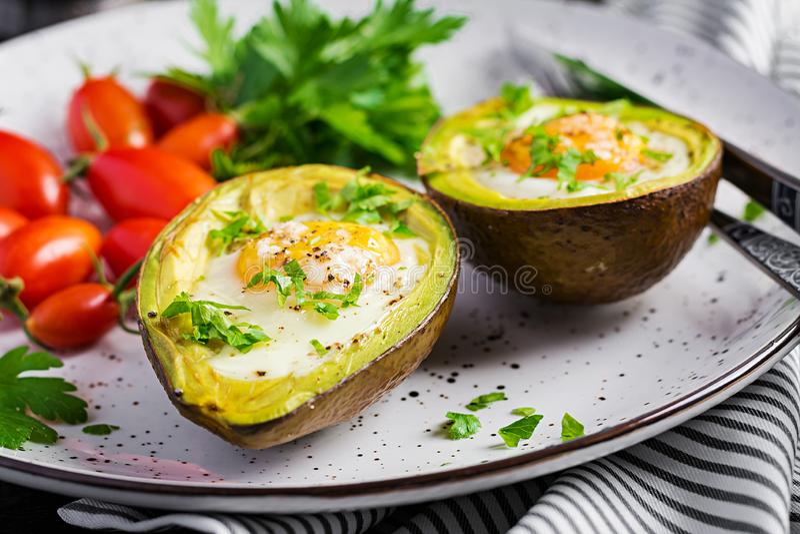 Avocado baked with egg and fresh salad. Vegetarian dish. Ketogenic diet. Keto food royalty free stock photos