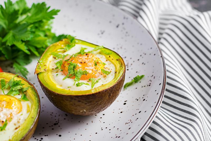 Avocado baked with egg and fresh salad. Vegetarian dish. Ketogenic diet. Keto food royalty free stock photography