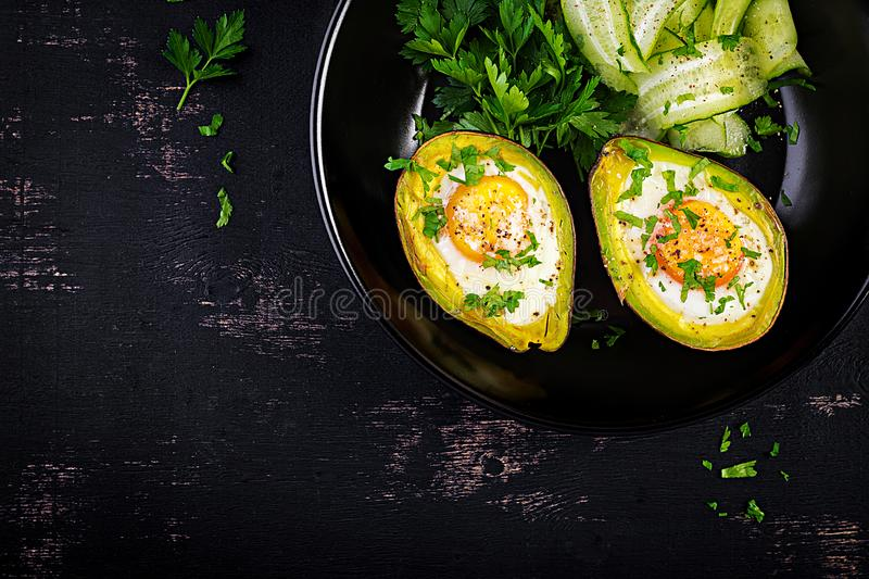 Avocado baked with egg and fresh salad. Vegetarian dish. Top view, overhead.  Ketogenic diet. Keto food stock photos