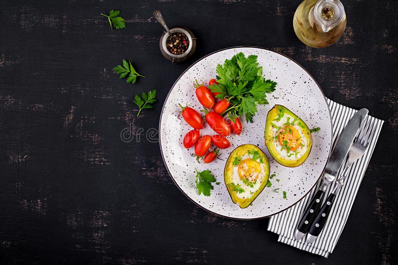 Avocado baked with egg and fresh salad. Vegetarian dish. Top view, overhead.  Ketogenic diet. Keto food royalty free stock photo
