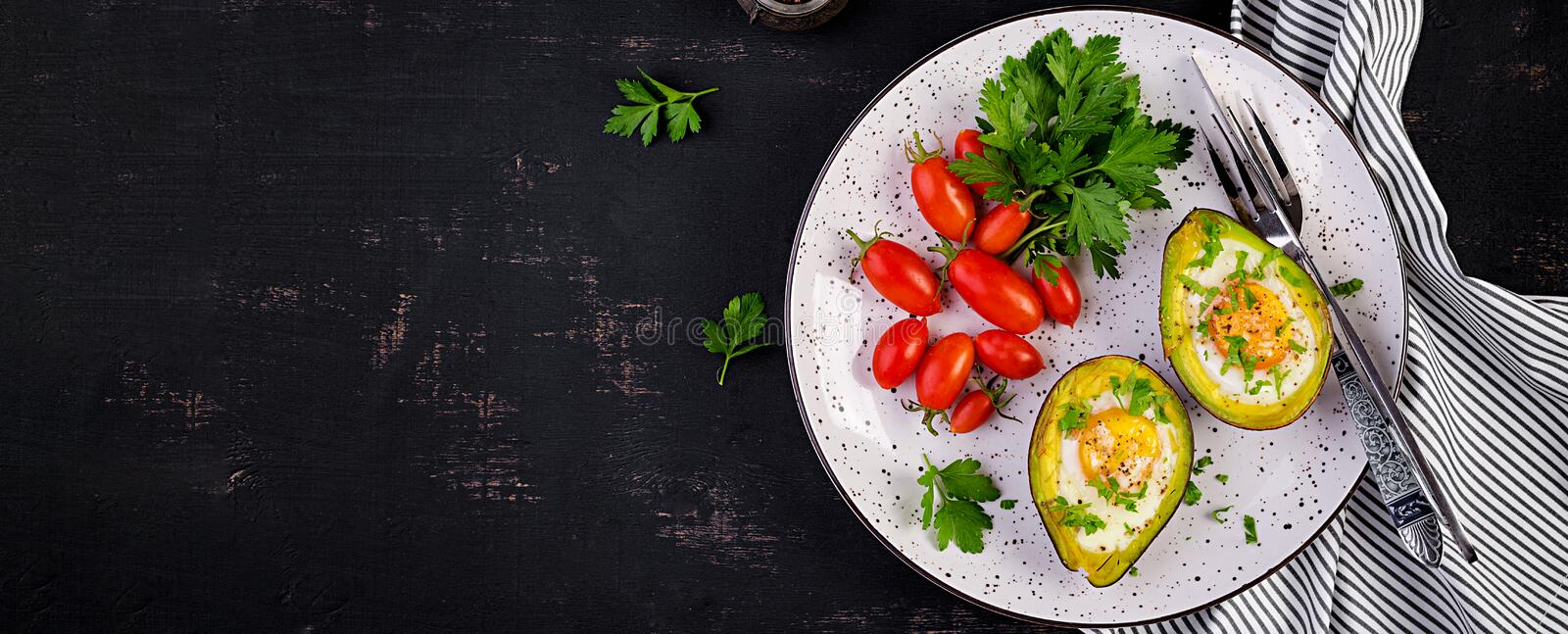 Avocado baked with egg and fresh salad. Vegetarian dish. Top view, overhead.  Ketogenic diet. Banner. Keto food stock photos