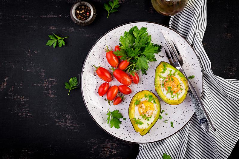 Avocado baked with egg and fresh salad. Vegetarian dish. stock images