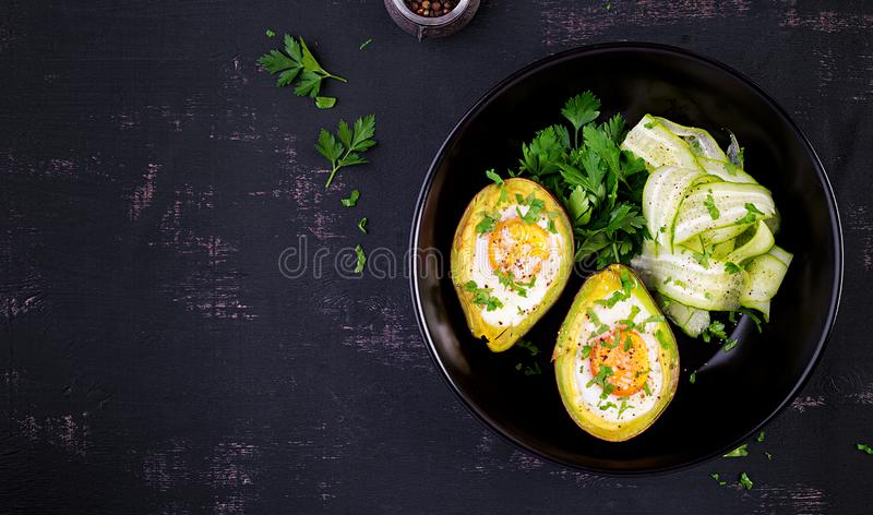 Avocado baked with egg and fresh salad. Vegetarian dish. Top view, overhead.  Ketogenic diet. Keto food stock photo