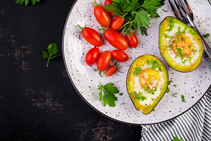 Avocado baked with egg and fresh salad. Vegetarian dish. Top view, overhead.  Ketogenic diet. Keto food stock image