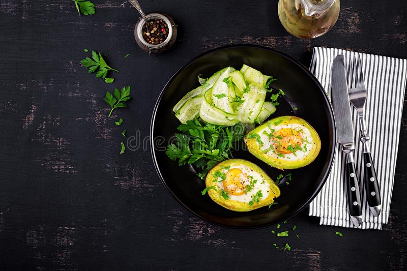 Avocado baked with egg and fresh salad. Vegetarian dish. Top view, overhead.  Ketogenic diet. Keto food stock photography