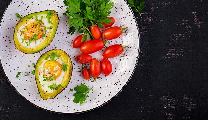 Avocado baked with egg and fresh salad. Vegetarian dish. Top view, overhead.  Ketogenic diet. Keto food stock images