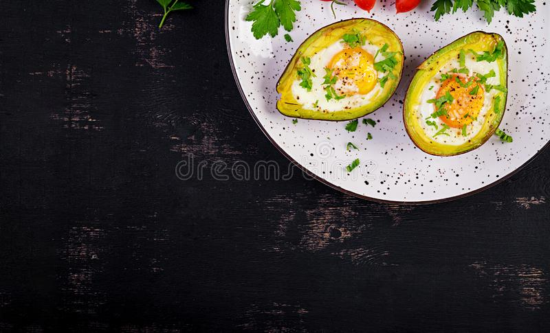 Avocado baked with egg and fresh salad. Vegetarian dish. Top view, overhead.  Ketogenic diet. Keto food royalty free stock image