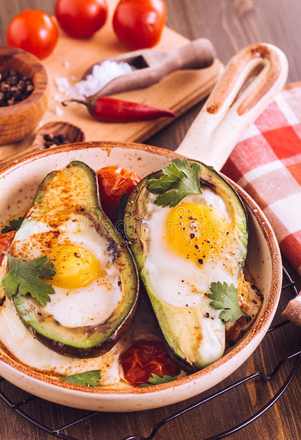 Avocado baked with egg on serving pan stock photo