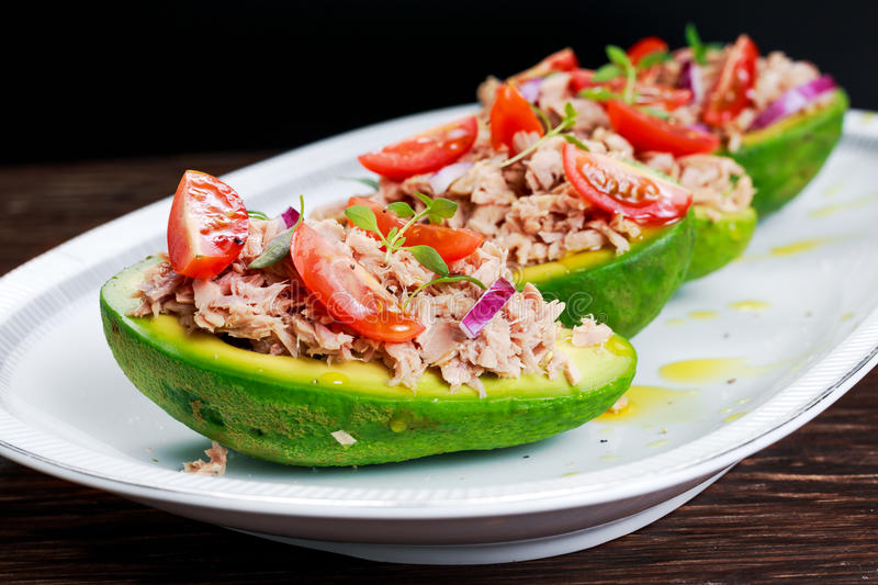 Avocado boats stuffed with tuna, red onion and cherry tomatoes. stock photo