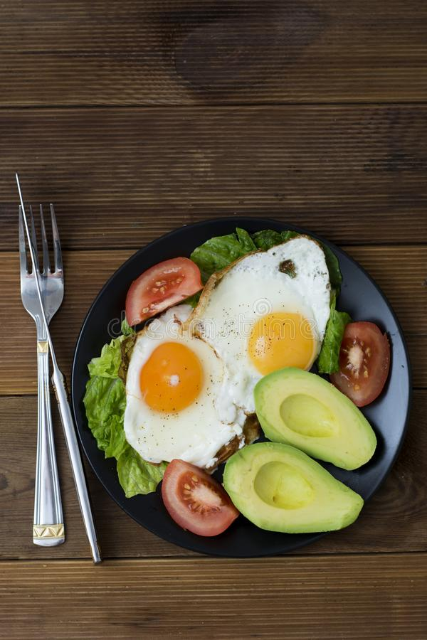 Avocado breakfast, fried eggs with whole grain toast bread on wooden background. Vertical image, top view stock images