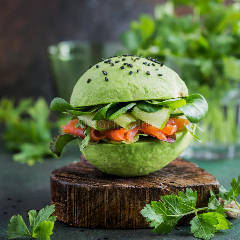 Avocado burger with salted salmon and fresh vegetables royalty free stock images