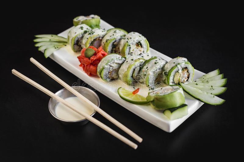 Avocado and cheese sushi roll with ceviche sauce on a black table royalty free stock image