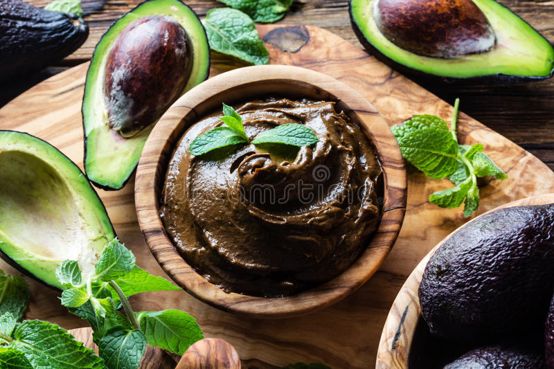 Avocado chocolate mousse in olive wooden bowl stock photo