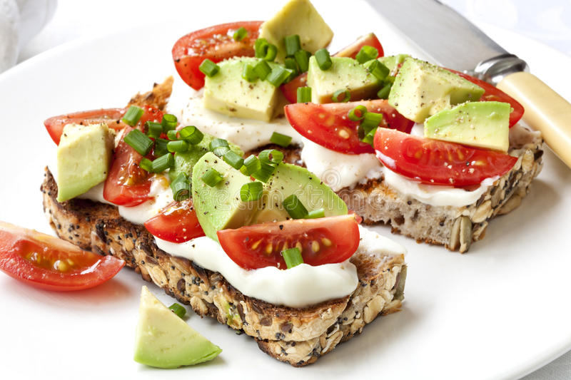 Avocado Cream Cheese and Tomatoes on Wholewheat Toast royalty free stock photos