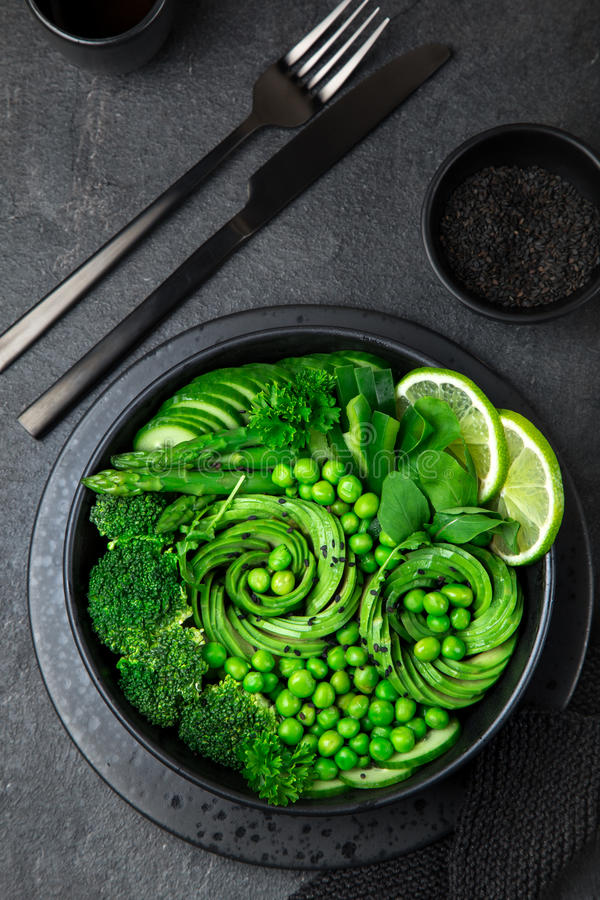 Avocado, cucumber, broccoli, asparagus and sweet peas salad, fresh green vegan detox lunch bowl. Black background. top view stock photo