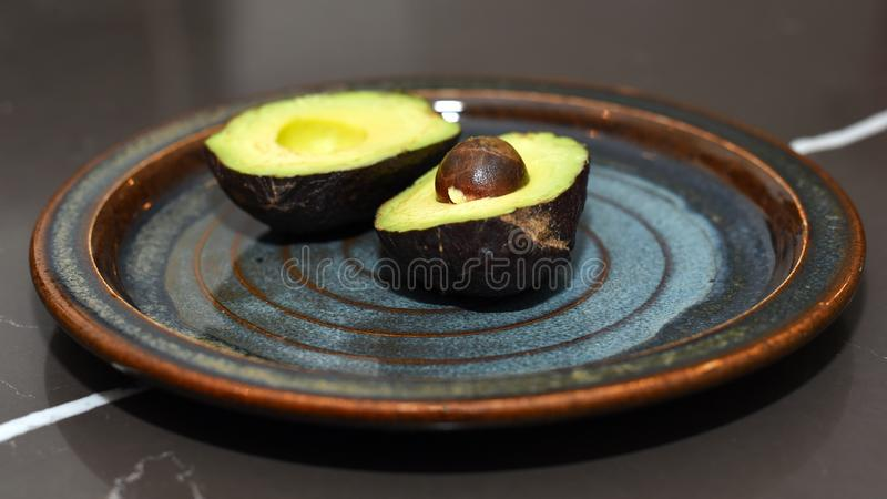 Avocado cut in half on plate royalty free stock photos