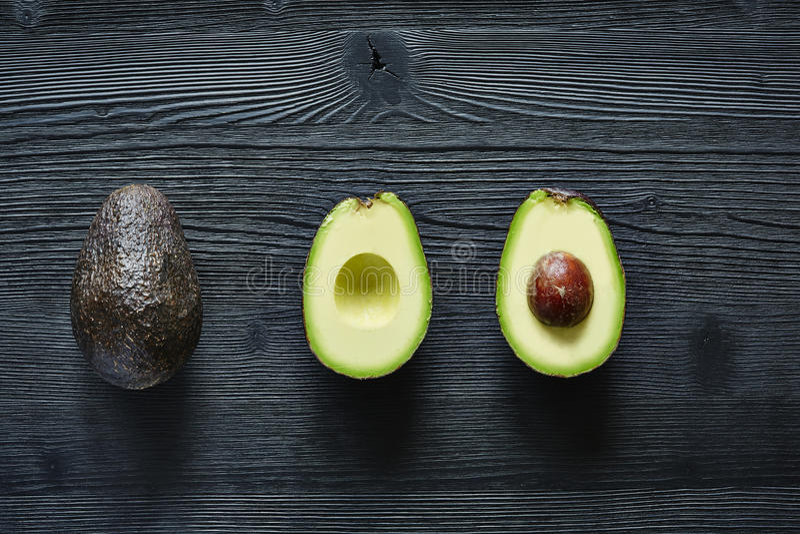 Avocado on dark wood. Three states of avocado original halfed and with stone green and black high contrast stock photo