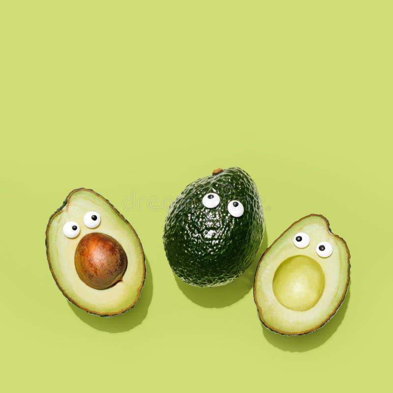 Avocado divertenti dei fronti su un fondo verde pastello fotografie stock