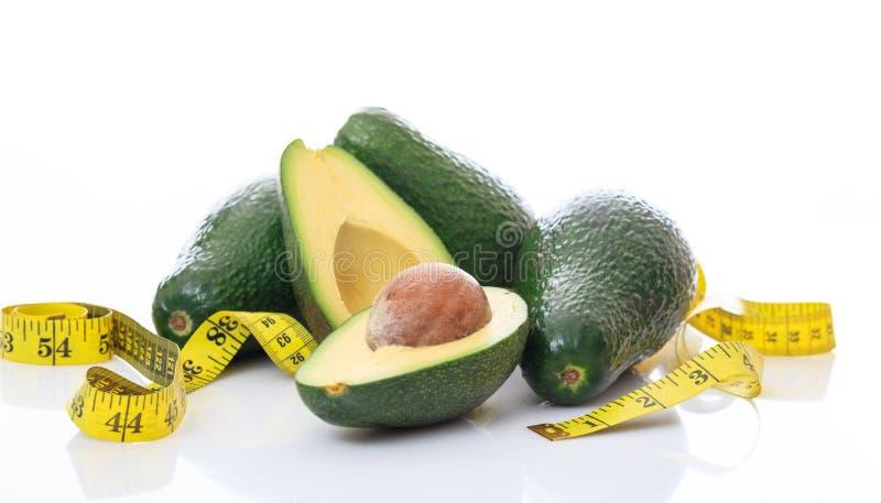 Avocado e nastro di misura su bianco immagini stock