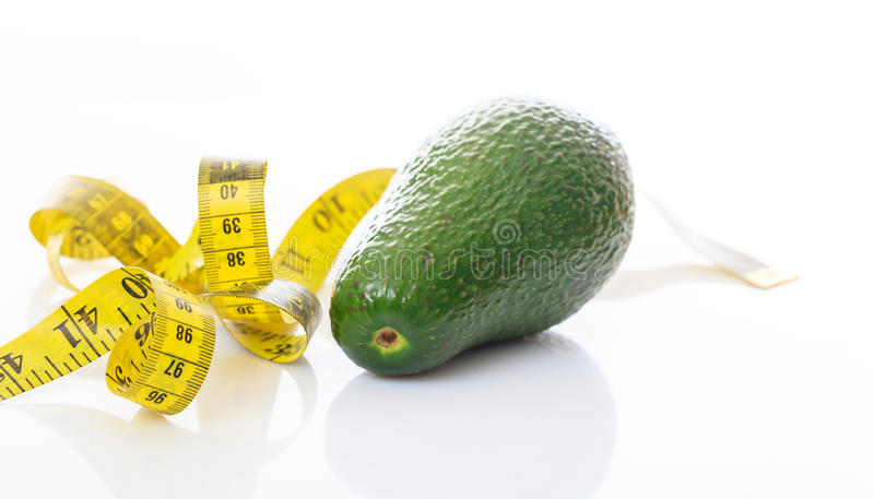 Avocado e nastro di misura su fondo bianco fotografia stock