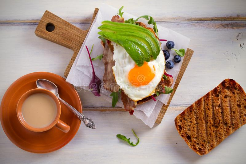 Avocado, egg and bacon sandwich. Fried egg and avocado on toast. Panini. Healthy tasty food for breakfast or brunch. stock images