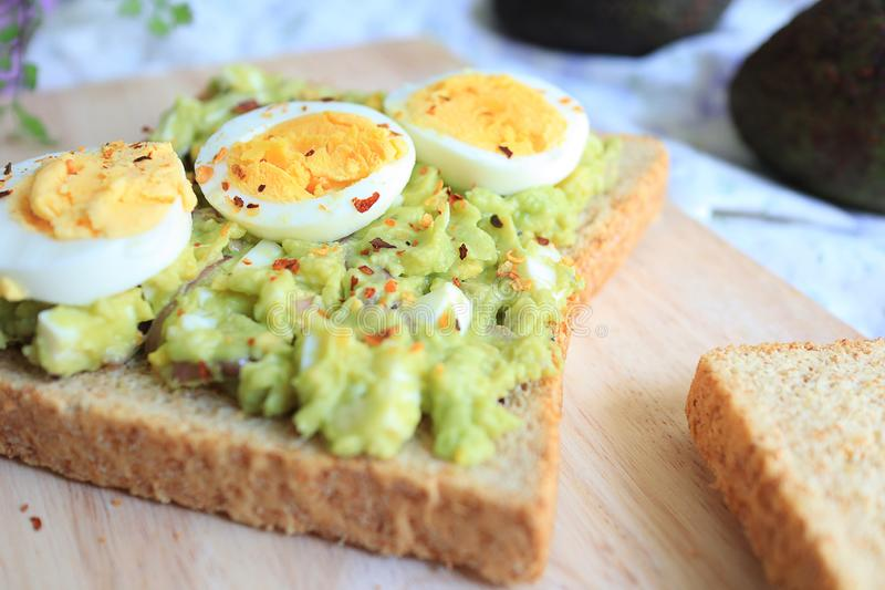 Avocado and egg toast on wooden. close up stock photos