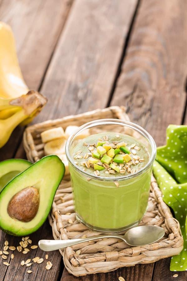 Avocado en banaan smoothie met haver met ingrediënten in glaskruik op houten achtergrond royalty-vrije stock fotografie